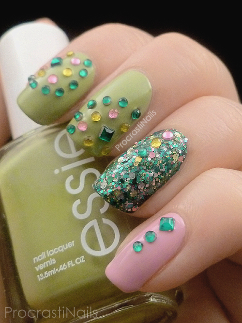 Nail art with green and pink polish and lots of gems