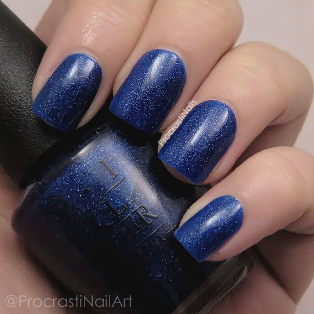 Swatch of a deep blue glitter nail polish with a hint of holo